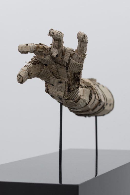 Grabing armsculpture on a plinth